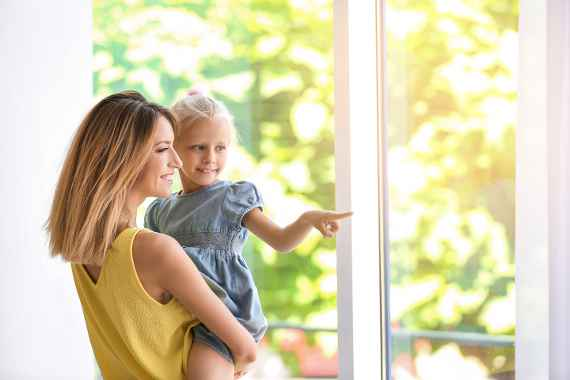 Young woman with cute little girl near window at home